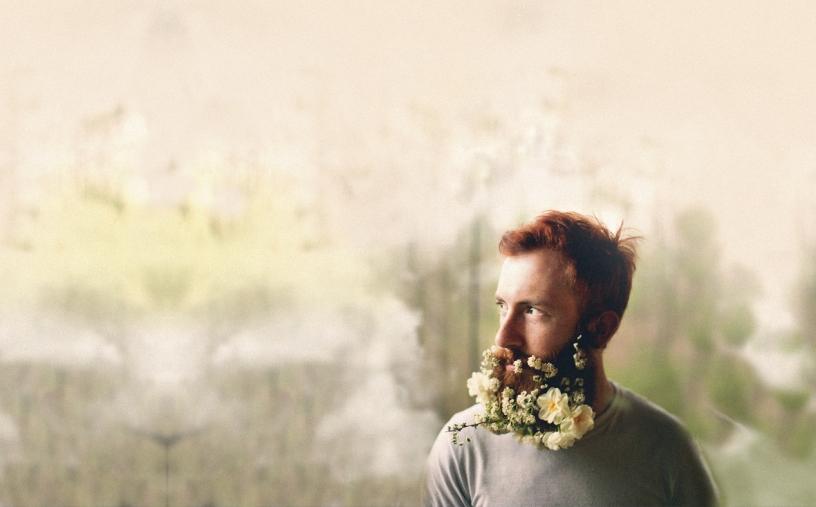 Hombre con flores en la barba